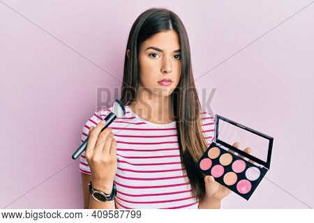 Young brunette woman holding makeup brush and blush palette relaxed with serious expression on face. simple and natural looking at the camera.