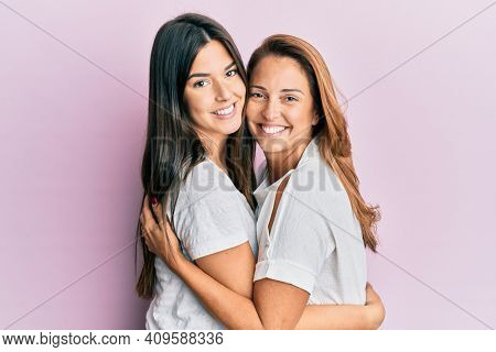Beautiful hispanic mother and daughter smiling happy hugging over isolated pink background.