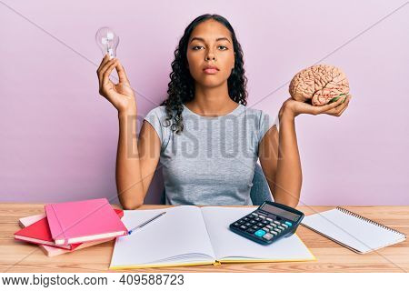 Young african american girl holding brain and light bulb studying for school relaxed with serious expression on face. simple and natural looking at the camera.