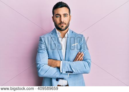 Young hispanic businessman wearing suit with arms crossed gesture relaxed with serious expression on face. simple and natural looking at the camera.