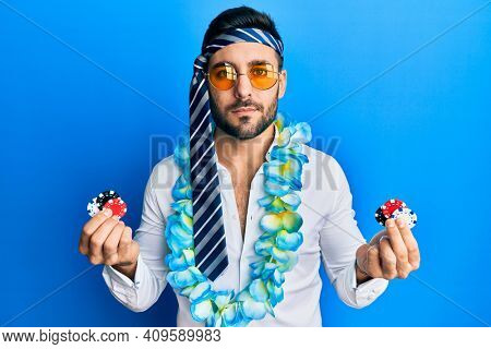 Young hispanic businessman wearing party funny style holding casino chips relaxed with serious expression on face. simple and natural looking at the camera.