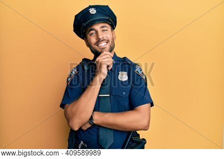 Handsome hispanic man wearing police uniform looking confident at the camera smiling with crossed arms and hand raised on chin. thinking positive.