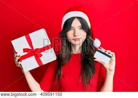Young beautiful caucasian girl wearing christmas hat, holding a gift and credit card relaxed with serious expression on face. simple and natural looking at the camera.