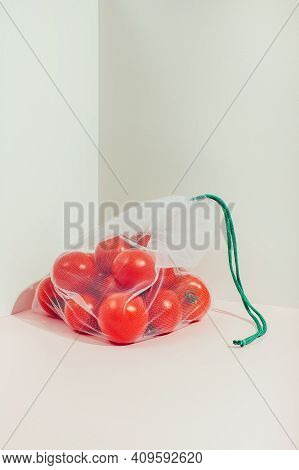 Reusable Packaging Of Products By Weight. Red Tomato In A Reusable Bag Close Up On A Pink Background