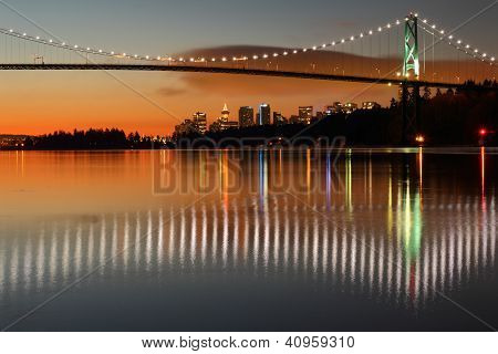 Dawn in Vancouver with the Lion's Gate Bridge crossing to Stanley park and reflecting in Burrard Inlet. The office towers of downtown Vancouver rise in the back ground. poster