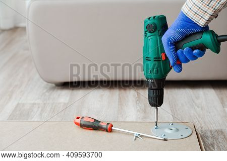Electric Drill Works In Handyman Hands At Home. Furniture Assembly Process, Master Collects Table Fu