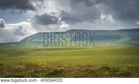People, Tourists Walking On Gravel Path Or Trail Towards Cuilcagh Mountain Park With Stormy, Dramati