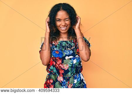 Young african american woman wearing casual clothes covering ears with fingers with annoyed expression for the noise of loud music. deaf concept.