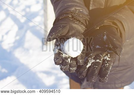 Round Snowball On Childs Palms Wearing Winter Gloves. Sun Lights During Frosty Winter Day. Protectio