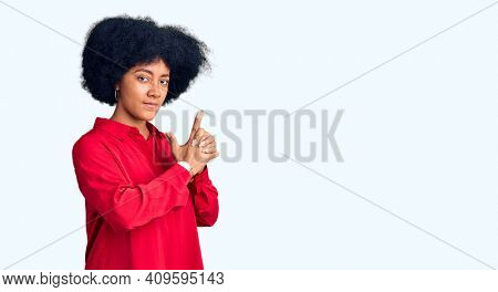Young african american girl wearing casual clothes holding symbolic gun with hand gesture, playing killing shooting weapons, angry face