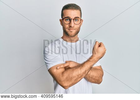 Young caucasian man wearing band aid for vaccine injection relaxed with serious expression on face. simple and natural looking at the camera.
