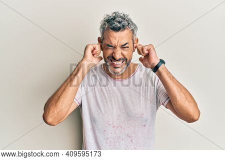Middle age grey-haired man wearing casual clothes covering ears with fingers with annoyed expression for the noise of loud music. deaf concept.
