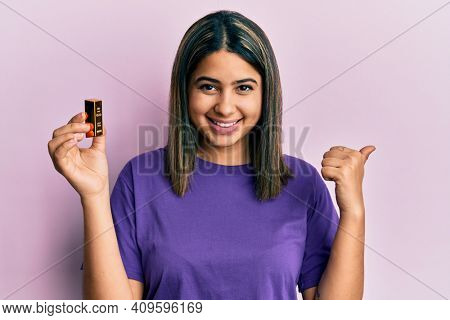 Young latin woman holding small gold ingot pointing thumb up to the side smiling happy with open mouth