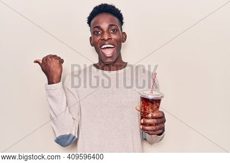 Young african american man drinking mate infusion pointing thumb up to the side smiling happy with open mouth