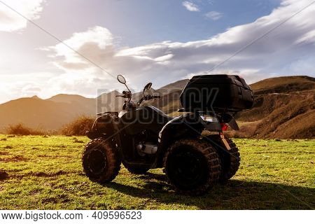View Of Atv Quad Bike Without Passenger In A Mountain Land In Sunset Summer. Off Road Awd Vehicle. A