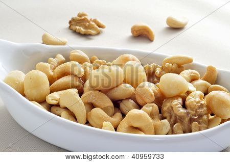 a bowl with mixed nuts, such as walnuts, macadamia nuts and cashews