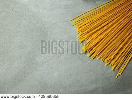 Yellow Long Spaghetti On Gray Background. Thin Pasta Arranged In Rows. Yellow Italian Pasta. Long Sp
