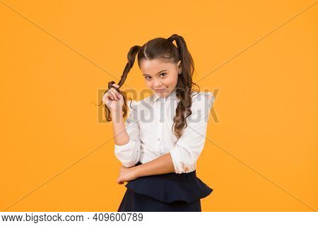 Modest Hairstyle. Cute Little Schoolchild Winding Hairstyle Around Her Finger On Yellow Background.