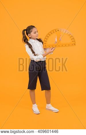 Setting Square With Protractor. Little Girl Using Triangle To Measure Angles In Degrees On Yellow Ba