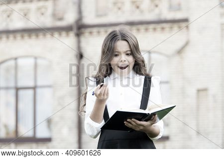 Keep Writing. Happy Little Girl With Textbook And Writing Pen Outdoor. Small School Child Practising