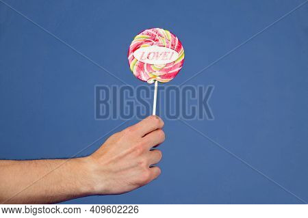 Sweet Feelings. Lollipop With Word Love. Male Hand Holds Lollipop With Inscription Love. Romantic Gi