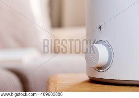 Woman Turns On The Modern Air Humidifier, Aroma Oil Diffuser At Home. Improving The Comfort Of Livin