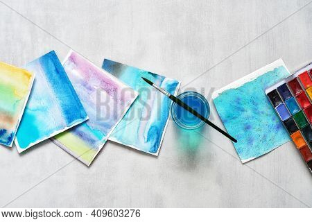 Set Of Paper Sheets Of Watercolor Patterns, Glass Of Water, Brush For Painting And Watercolor Paints