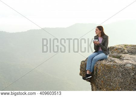 Pensive Woman Drinking Coffee Contemplating Views From The Top Of A Cliff In The Mountain