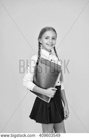 Basic Level. Happy Schoolgirl Hold Textbooks Yellow Background. Little Schoolgirl Back To School. Sm