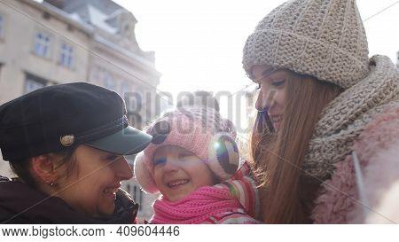 Lesbian Couple Tourists Posing, Taking Selfie With Adoption Child Girl Kid On City Street. Two Women