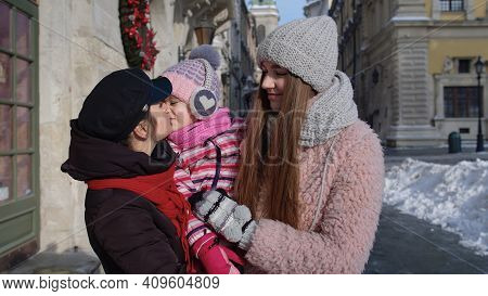 Lovely Sisters Holding Younger Sister Child Girl In Hands. Tourists Family Talking, Smiling, Embraci