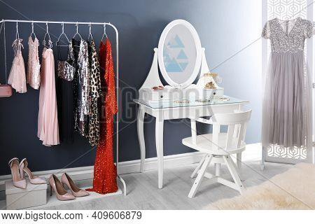 Rack With Collection Of Beautiful Festive Clothes And Dressing Table In Stylish Room Interior