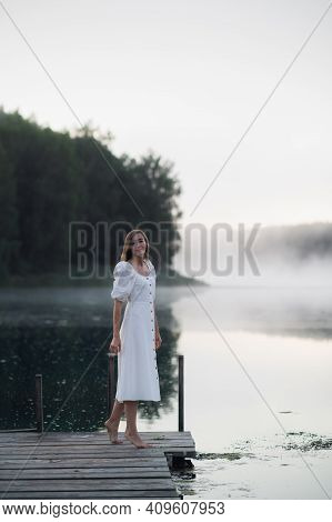 Tender Romanitc Sentimental Female Lady In The Morning On A Wooden Pier Near The Misty River In A Wh