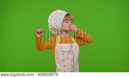 Charming Child Girl Kid Dressed In Apron And Hat Like Chef Cook Baker Raising Hands, Showing Tasty G