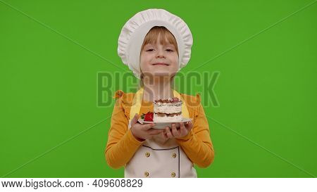 Portrait Of Little Child Girl Kid Dressed As Professional Cook Chef Baker Eating Tasty Strawberry Ca