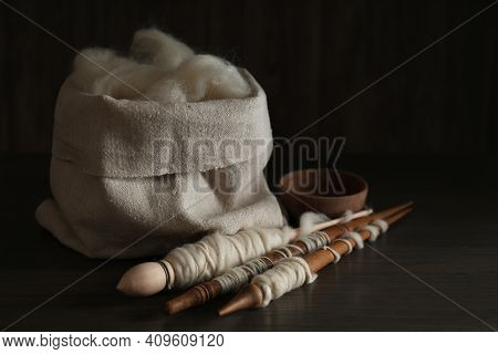 Soft White Wool And Spindles On Wooden Table