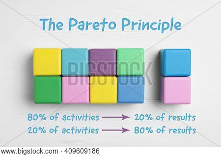Flat Lay Composition With Colorful Cubes On White Wooden Background. Pareto Principle Concept
