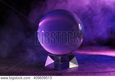 Crystal Ball On Table And Smoke Against Dark Background. Predictions Of Future