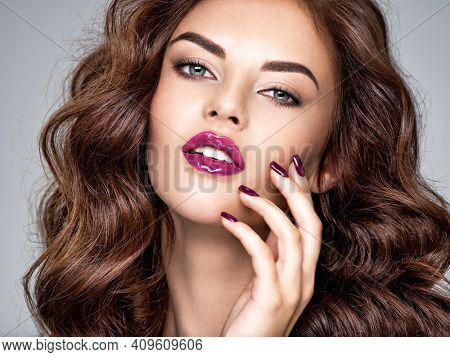 Beautiful and stunning woman with bright purple lipstick on lips and fingernails.  Young caucasian gorgeous adult girl with long brown hair. Model. Closeup woman's portrait.