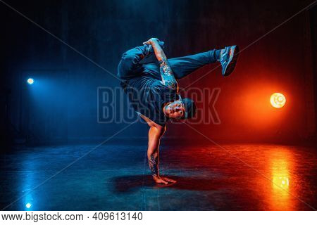 Young man break dancing in dark hall with blue and red lights. Tattoo on hands.