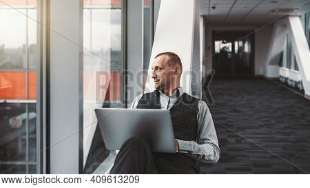 A Portrait Of A Serious Relaxed Elegant Man Entrepreneur With A Laptop, Sprawled On A Bench Of A Mod