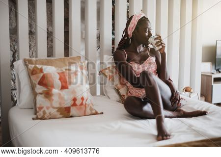A Sensual Young Black Woman In A Nighty Is Drinking A Morning Tea While Sitting On A White Bed In A