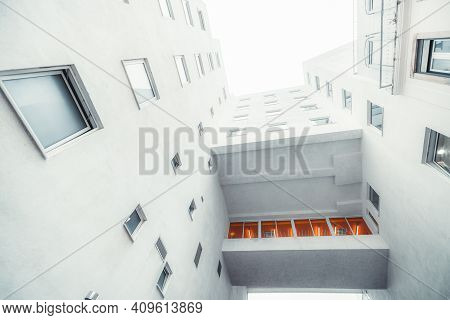 A Wide-angle View From The Bottom Of A White Modern Residential House With An Illuminated By An Oran