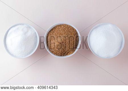 White Sugar, Cane Sugar And Sugar Substitute In Bowls Top View.