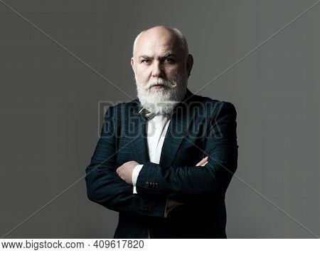 Serious Senior Man In Suit With Arms Crossed. Bearded Middle-aged Man With A Serious Expression In A