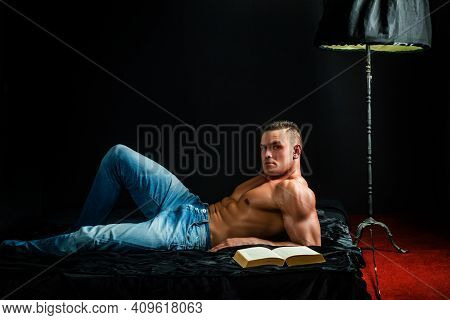 Muscular Shirtless Man In Bedroom Reading. Macho Naked In Bed. Sex And Relaxation Concept. Book Love