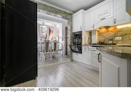 Modern classic luxury white kitchen interior with dining zone, electric and microwave ovens doors are open