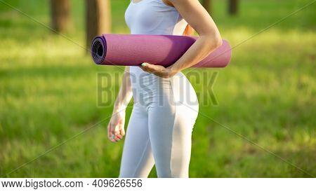 Exercising On Mat In Morning Sunshine. Woman Rolling Yoga Mat. Female Hands Unrolling Yoga Mat Befor