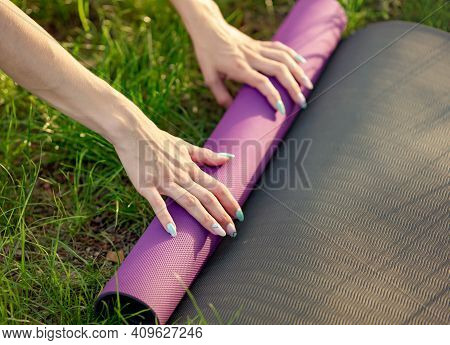 Fit Woman Folding Exercise Mat Before Or After Working Out In The Park. Cropped Image Of Female Putt