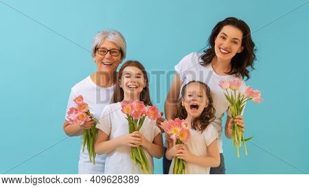 Happy women's day! Children daughters are congratulating mom and grandma giving them flowers tulips.Granny, mum and girls smiling on blue wall background. Family holiday and togetherness.
